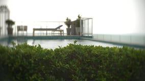 Vista de la piscina en el tejado que pasa por alto el mar 4k, falta de definici?n del fondo almacen de metraje de vídeo