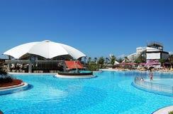 Vista de la piscina y de la barra azules debajo del paraguas blanco grande en h turco Foto de archivo