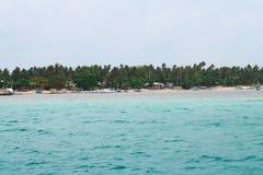 Vista de la playa blanca de la arena a distancia con verdes alineados y árboles en el fondo Imagen de archivo