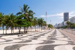 Vista de la playa de Copacabana con las palmas y del mosaico de la acera en Rio de Janeiro Fotos de archivo libres de regalías