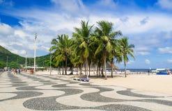 Vista de la playa de Copacabana con las palmas y del mosaico de la acera en Rio de Janeiro Fotografía de archivo
