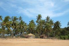 Vista de la playa, de las casas de verano y de las palmeras Fotos de archivo
