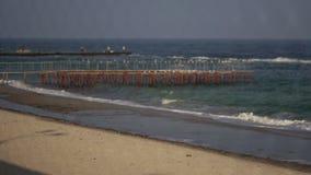 Vista de la playa a través de la cerca de la rejilla almacen de metraje de vídeo
