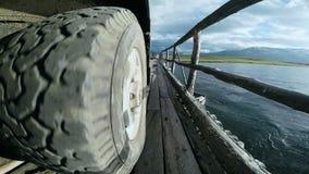 Vista de la rueda del coche que pasa sobre el puente Viaje auto: SUV monta en el puente de madera viejo en una alta montaña almacen de metraje de vídeo
