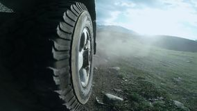 Vista de la rueda de un coche que viaja a lo largo de un valle en un campo SUV monta en un camino de la alta montaña sobre un río almacen de video