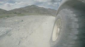 Vista de la rueda de un coche que viaja a lo largo de un valle Viajes en coche rápidamente en una carretera nacional áspera SUV m almacen de video