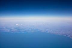 Vista de la tierra del avión, del cielo azul y del mar Foto de archivo libre de regalías