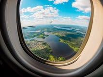Vista de la tierra del planeta a través de la porta del aeroplano foto de archivo