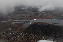Vista de la tierra de un aeroplano En la cima de las nubes blancas en la parte inferior del río, cabañas, bosque, embarcadero del fotografía de archivo libre de regalías