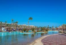Vista de la zona de recreo de los hotel's en la playa y la orilla de mar, palmeras debajo del cielo azul de un día soleado foto de archivo