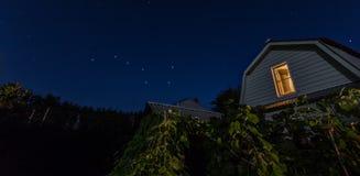 Vista de las estrellas del cielo nocturno del cazo grande en el villiage con la casa y de árboles en el primero plano Foto de archivo libre de regalías