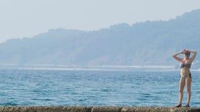 Vista de las islas en la bahía Tiro del Telephoto la mujer en el rompeolas mira la costa en la niebla, 4k, lento metrajes