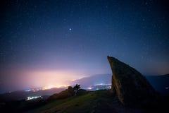 Vista de las luces de la ciudad y del cielo estrellado de un pico de montaña imagenes de archivo