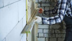 Vista de las manos del constructor en guantes usando la regla de la construcción para enyesar fotos de archivo libres de regalías