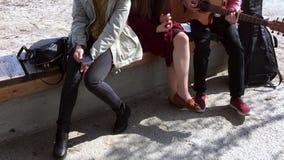 Vista de las piernas de muchachas y un individuo que se est?n sentando en un banco fuera de la casa Juventud en el aire fresco almacen de video