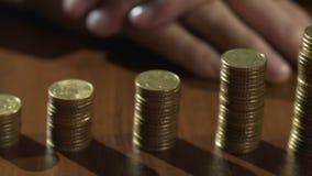 Vista de las pilas crecientes de la moneda en fila en la tabla con la arena que fluye en reloj de arena almacen de video