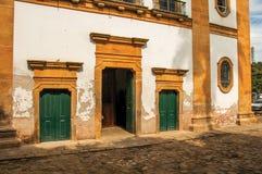 Vista de las puertas de la iglesia y de la calle coloreadas viejas del guijarro en Paraty Foto de archivo