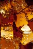 Vista de los cubos de hielo en fondo de la cola Fotografía de archivo libre de regalías