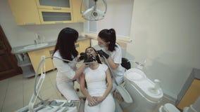 Vista de los dientes femeninos que limpian el tratamiento en gabinete dental almacen de metraje de vídeo