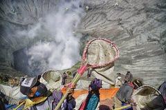Vista de los locals que intentan coger los sacrificios lanzados en el cráter del soporte Bromo durante el festival de Kasado Fotos de archivo libres de regalías
