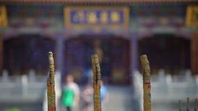 Vista de los palillos ardiendo del incienso en templo chino metrajes