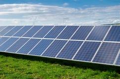 Vista de los paneles fotovoltaicos solares en un prado con la hierba y los dientes de león en la ciudad debajo del cielo azul con Foto de archivo libre de regalías