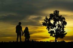 Vista de los pares jovenes que caminan a lo largo de la orilla durante puesta del sol Imagen de archivo libre de regalías