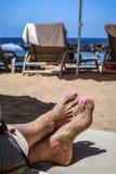 Vista de los pies de una mujer en silla de cubierta en una playa imágenes de archivo libres de regalías