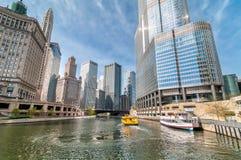 Vista de los rascacielos de Chicago con el barco de visita turístico de excursión de Watertaxi y de Wendell que cruza en el río C fotos de archivo libres de regalías