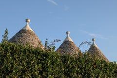 Vista de los tejados de piedra secos cónicos de un grupo de casas del trullo detrás de un seto fuera de Alberobello, Puglia, Ital fotos de archivo libres de regalías