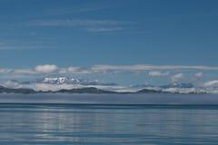 Vista de montañas coronadas de nieve y de nubes blancas bajas antes del cielo azul y del mar tranquilo reflector del ` s de Canad Foto de archivo libre de regalías