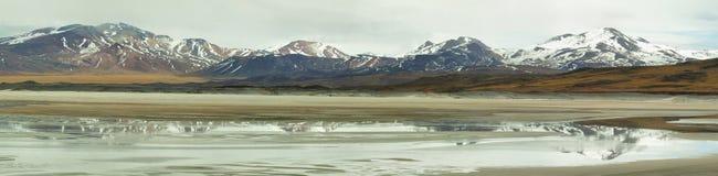 Vista de montañas y de los calientes de los Aguas o lago de sal de Piedras Rojas en el paso de Sico Fotos de archivo libres de regalías