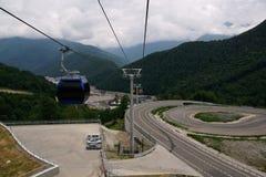 Vista de montañas y funicular con una cabina Imagenes de archivo