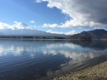 Vista de Mt Fuji con el cielo azul claro, las nubes y el lago liso emergen en Kawaguchiko, Yamanashi, Japón foto de archivo