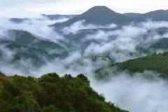 Vista de niebla de una montaña y de un pueblo Imagen de archivo libre de regalías