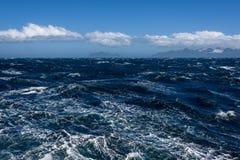 Vista de Océano Atlántico y de las montañas distantes, agua picada, cielo azul tranquilo con las nubes blancas imagen de archivo libre de regalías