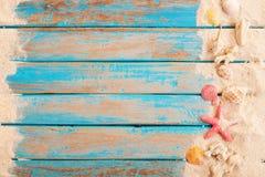 Vista de Op. Sys. de la arena de la playa con las cáscaras, estrellas de mar en el tablón de madera en el mar azul Fotografía de archivo libre de regalías