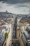 Vista de París, Rue Saint-Roch con la basílica de Sacre Coeur en el fondo imagenes de archivo