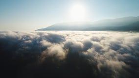 Vista de partes superiores bonitas e do vale da montanha enchidos com as nuvens encaracolados contra o c?u azul e o sol brilhante foto de stock