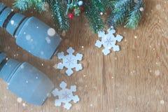 Vista de pesos azuis do gym, de ramos de pinheiro nevados e de decoração do Natal no fundo de madeira fotografia de stock royalty free