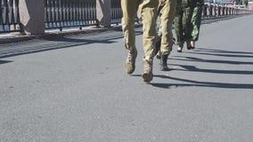 Vista de pies masculinos y femeninos corrientes en uniforme militar en el asfalto Mujer en los talones Día asoleado metrajes