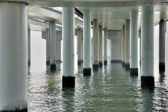 Vista de pilas y del agua bajo plataforma del puente Foto de archivo