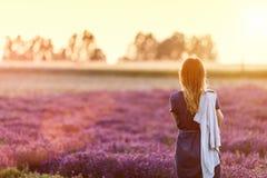 Vista de relaxamento da jovem mulher no campo da alfazema no por do sol foto de stock