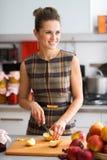 Vista de sorriso da mulher na distância ao cortar maçãs Fotos de Stock Royalty Free