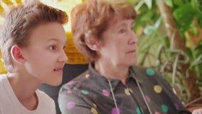Vista de sorriso superior do menino da mulher e do adolescente a indicar filme