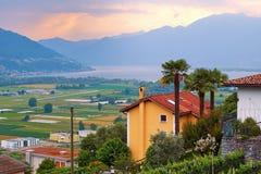 Vista de Suiza meridional rural con las casas, las granjas, los viñedos, las montañas y el lago Maggiore de las montañas fotografía de archivo