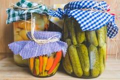 Vista de tarros con las verduras conservadas en vinagre con las cubiertas a cuadros coloridas del tarro fotografía de archivo