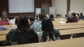 Vista de trás de um grande grupo misturado da afiliação étnica de estudantes em uma sala de aula, estudantes interessados em leit filme
