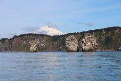 Vista de tri Brata con el top del volcán de Koryaksky en el fondo imagenes de archivo