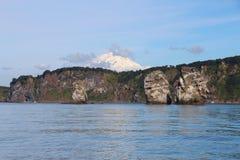 Vista de tri Brata con el top del volcán de Koryaksky en el fondo imágenes de archivo libres de regalías